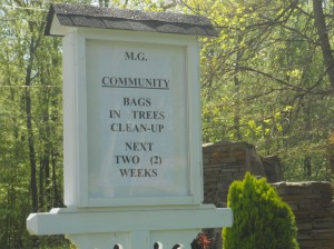 Community bags in trees clean up sign